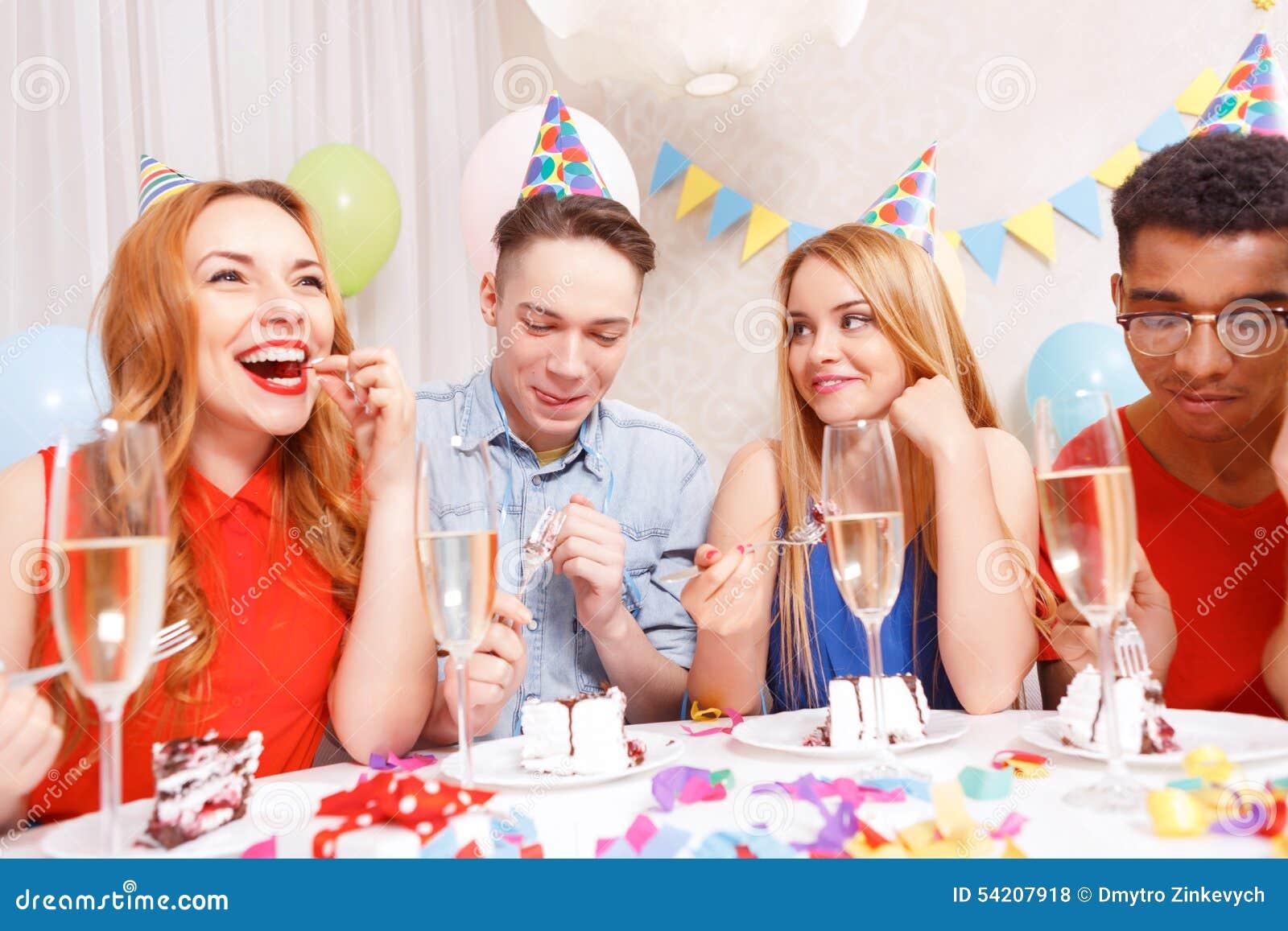Młodzi ludzie świętuje urodzinowego obsiadanie przy