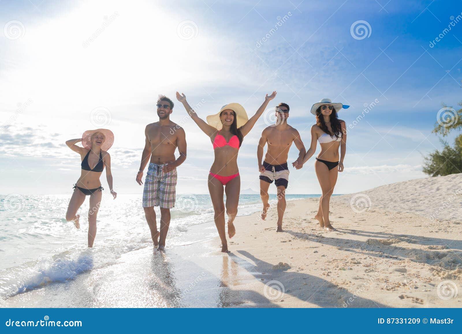 Młodzi Ludzie Grupują Na Plażowym wakacje, Szczęśliwi Uśmiechnięci przyjaciele Chodzi nadmorski