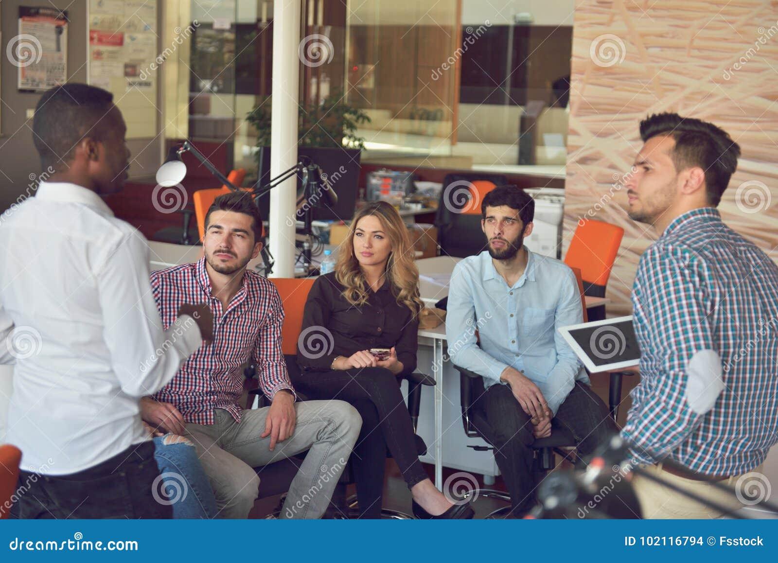 Młodzi ludzie grupują w nowożytnym biurze drużynowego spotkania i brainstorming podczas gdy pracujący na laptopie i pijący kawę