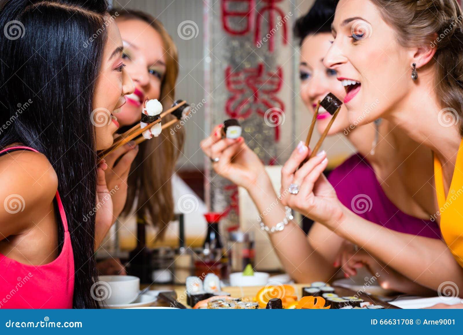 Młodzi ludzie je suszi w restauraci
