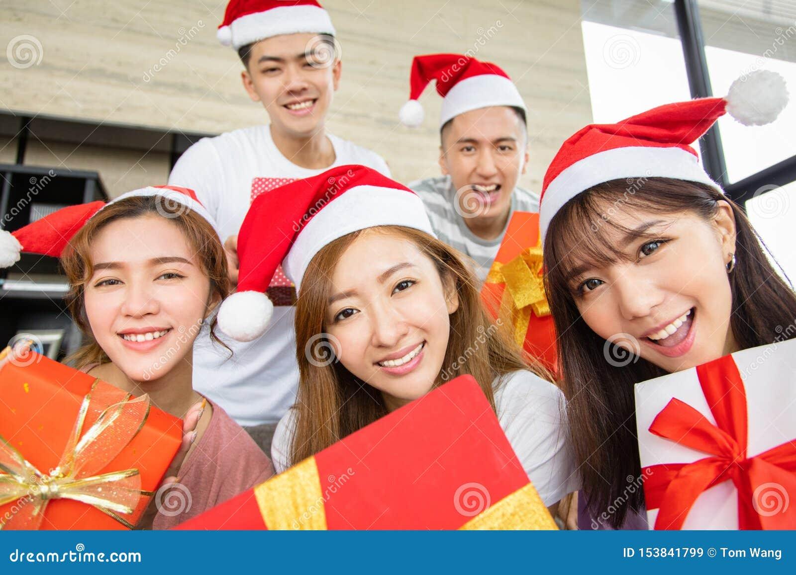 Młodzi ludzie ma zabawę i pokazuje boże narodzenie prezent