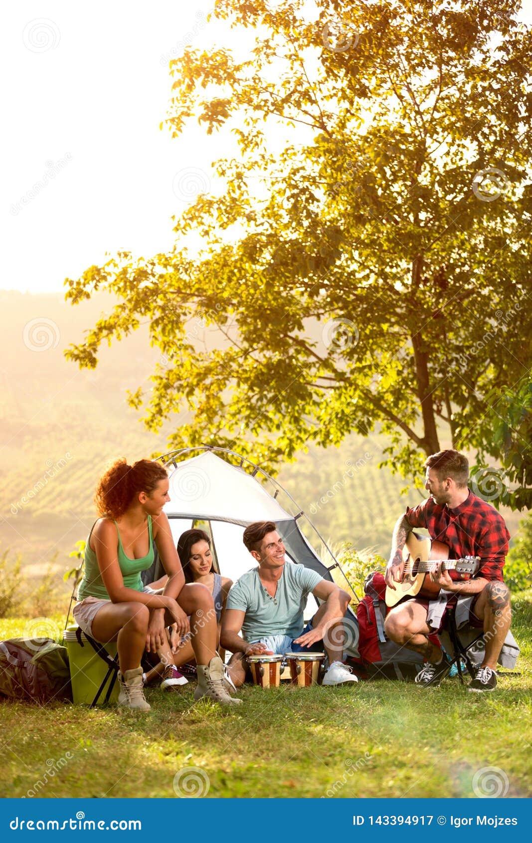 Młodzi ludzie na campingowej wycieczce bawić się i śpiewać