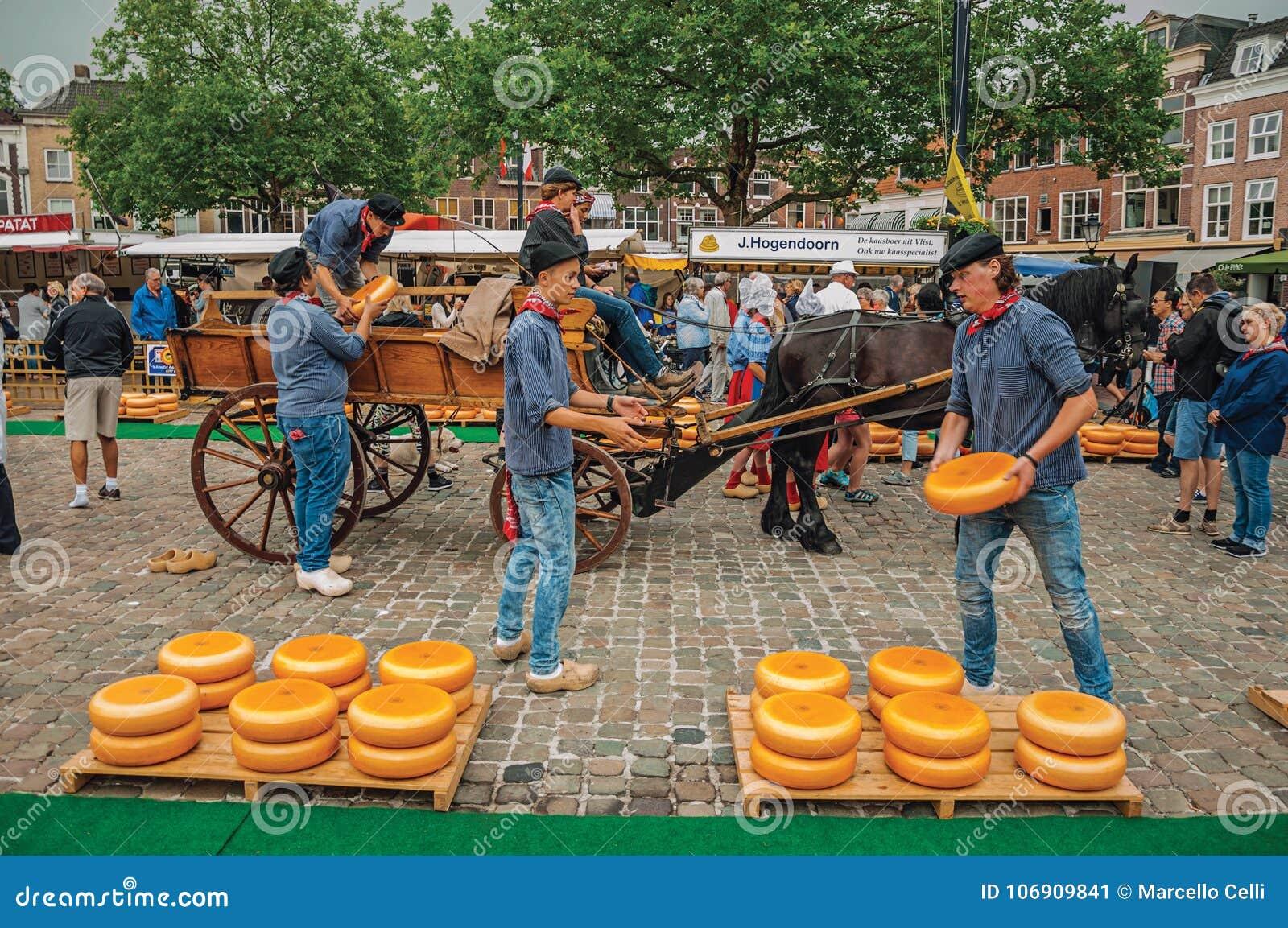 Młodzi ludzie niesie furę z serem przy końcówką Targowego kwadrata jarmark w Gouda