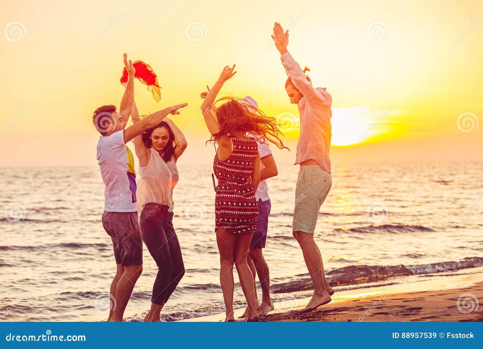 Młodzi Ludzie Tanczy Na plaży przy zmierzchem