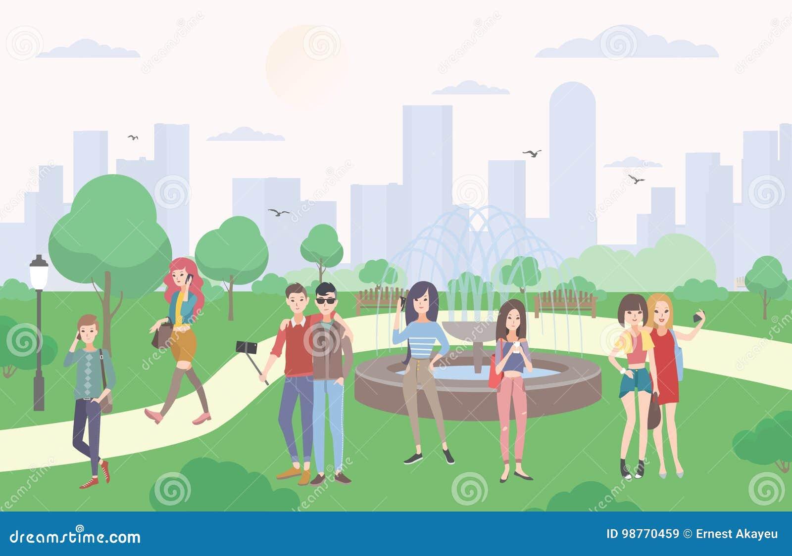 Młodzi ludzie z gadżetami w parku Faceci i dziewczyny komunikuje smartphone i urządzeniami przenośnymi, robią selfie