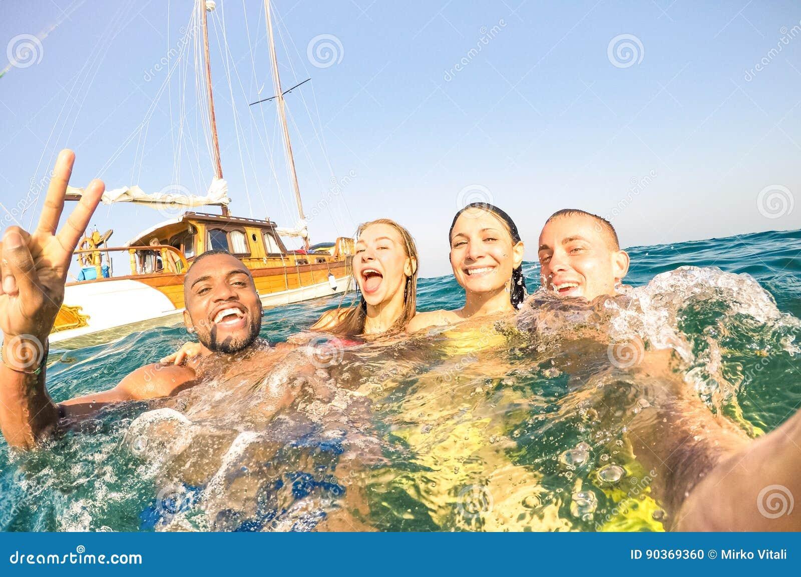 Młodzi multiracial przyjaciele bierze selfie i dopłynięcie na żeglowanie łodzi objeżdżają