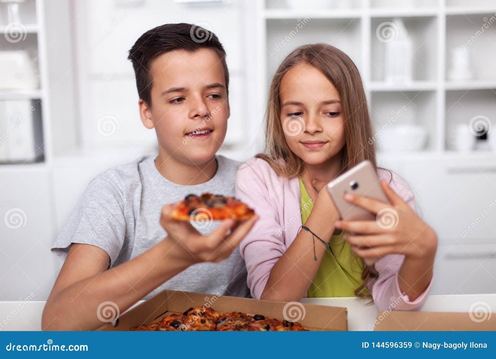 Młodzi nastolatkowie bierze selfie z ich pizzą w kuchni