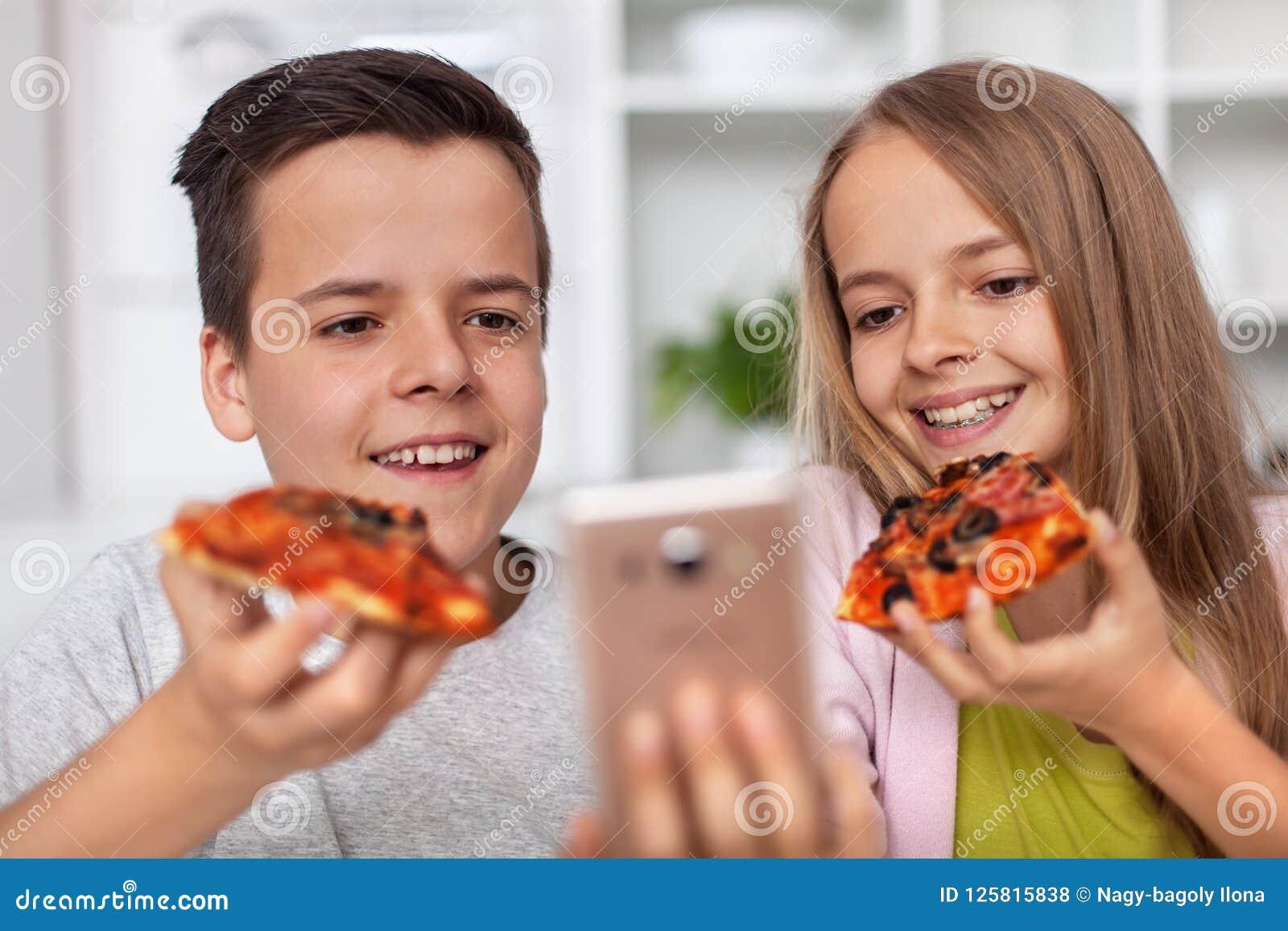 Młodzi nastolatkowie je pizza plasterki i bierze selfie