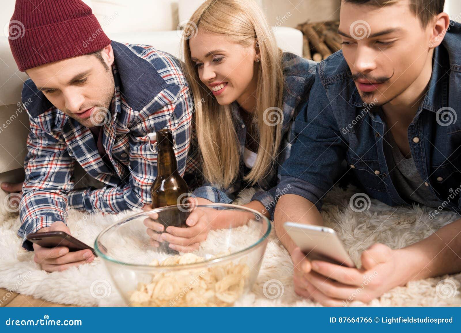 Młodzi przyjaciele kłama na dywanie i używa smartphones podczas gdy pijący piwo