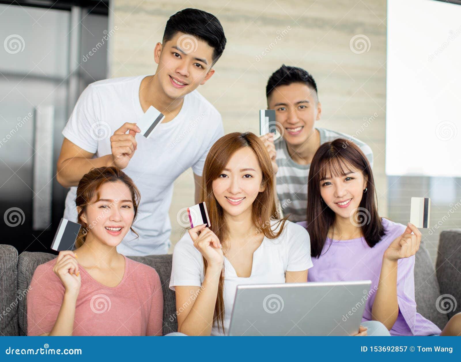 Młodzi przyjaciele kupuje na linii z kartą kredytową i laptopem