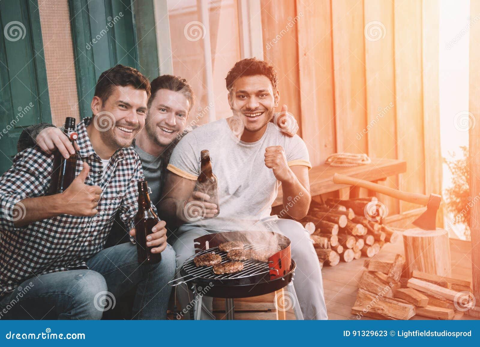 Młodzi przyjaciele robi grillowi i pije piwo na ganeczku z plecy światłem