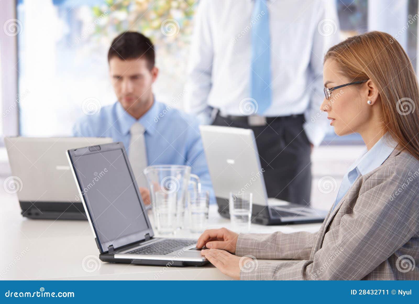 Młodzi przypadkowi urzędnicy pracuje na laptopie