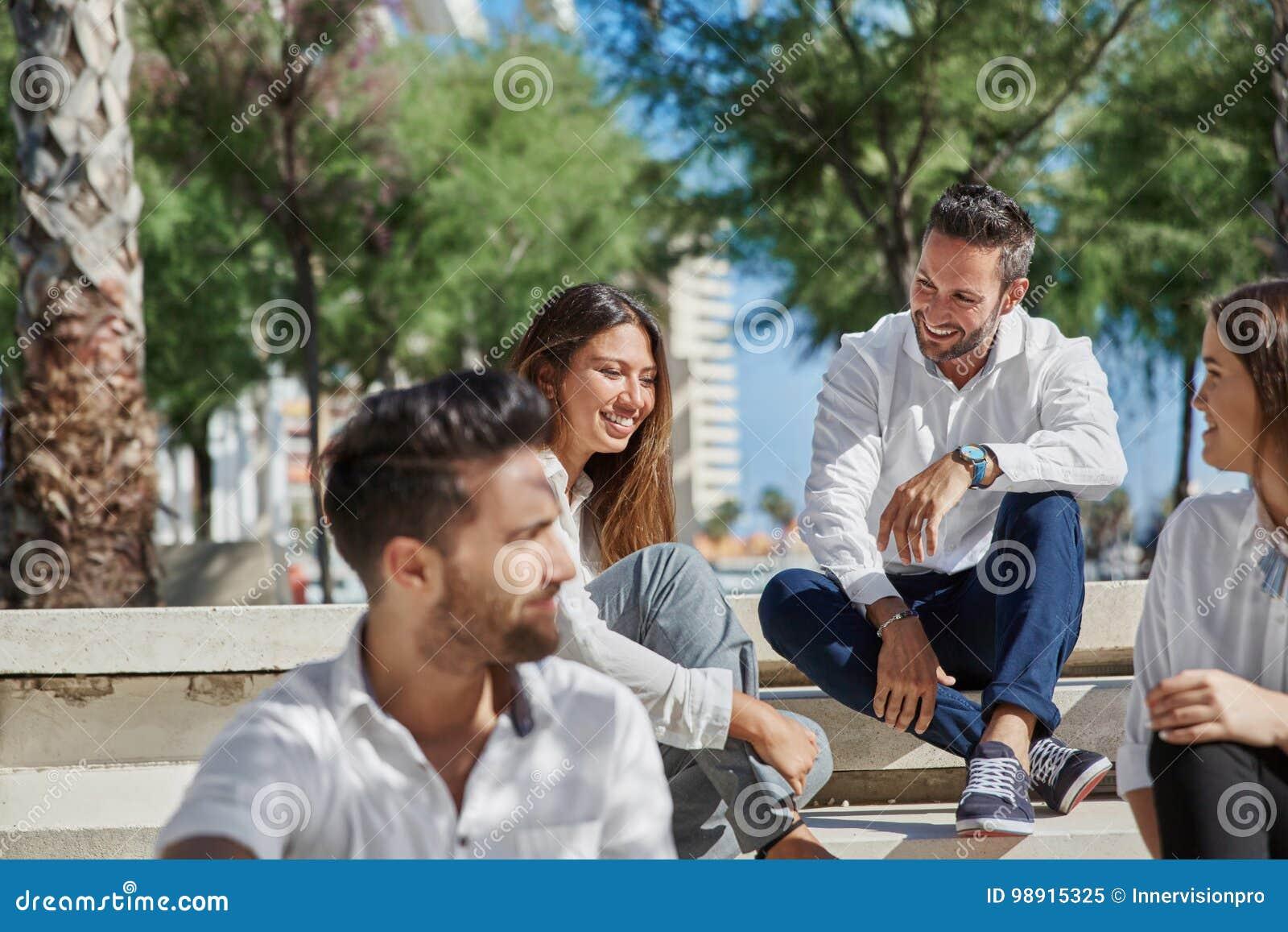 Młodzi szczęśliwi ludzie siedzi wpólnie outside śmiać się