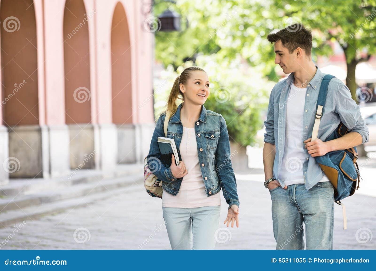 Młodzi szkoła wyższa przyjaciele opowiada podczas gdy chodzący przy kampusem