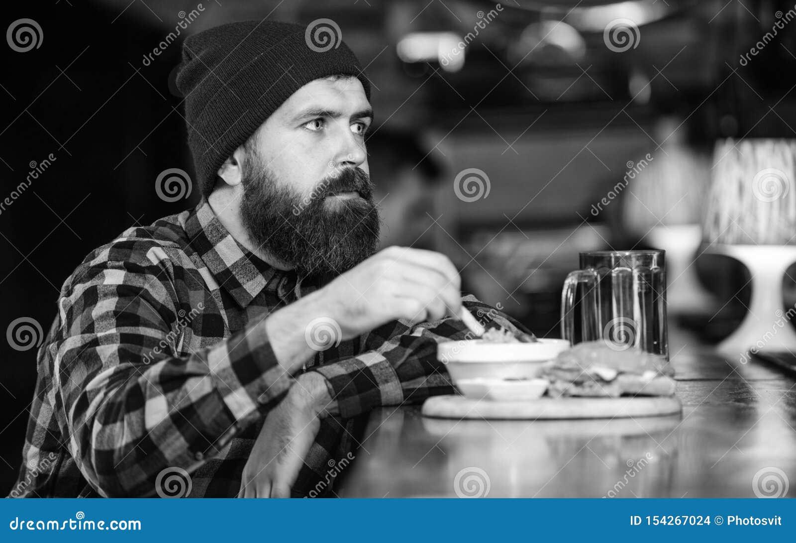 M??czyzna z brod? je hamburgeru menu Brutalnego modnisia brodaty m??czyzna siedzi przy baru kontuarem Nabranie posi?ek Wysoki kal