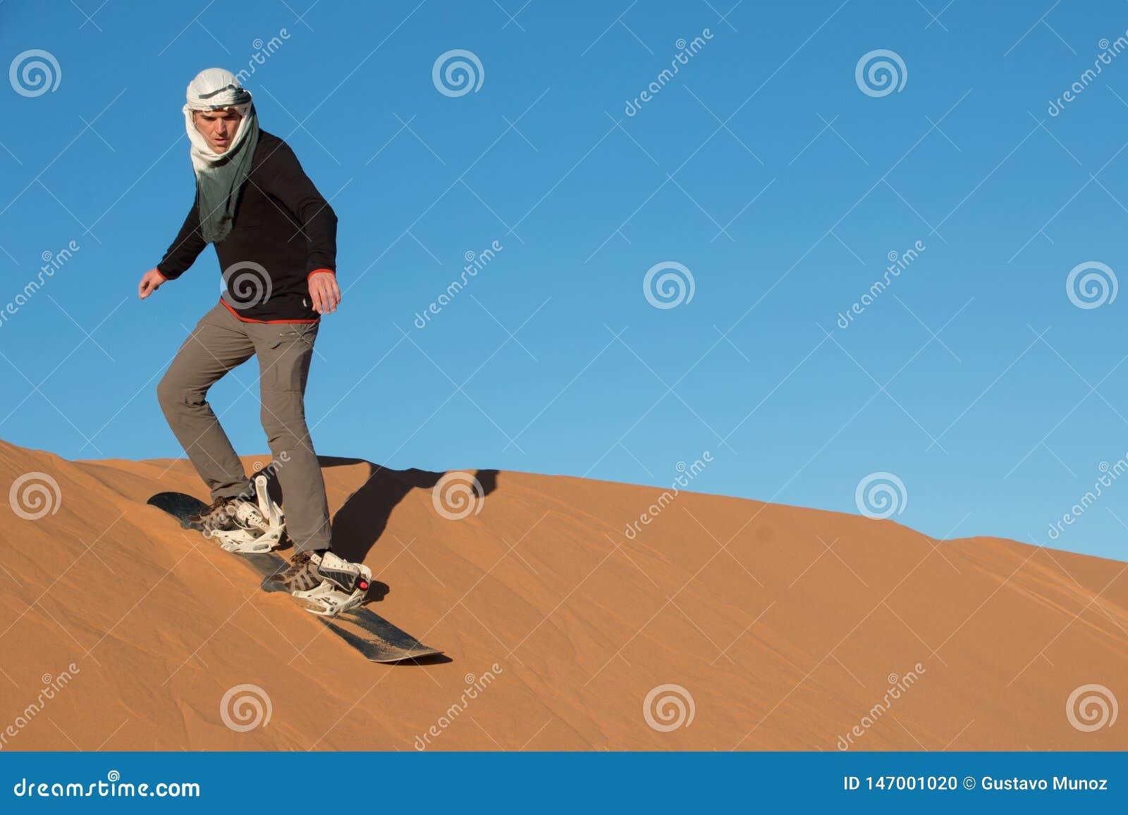 M??czyzna z chustki na g?ow? ?wiczy sandboarding w pustynnych diunach erg Chebbi
