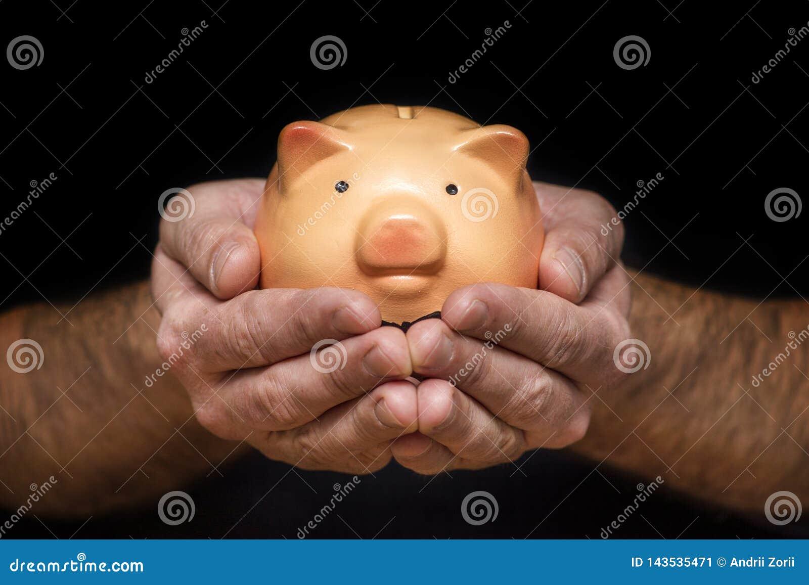 M??czyzna z prosi?tko bankiem w r?ce M??czyzna trzyma prosi?tko banka w jego r?kach dla pieni?dze lub finanse poj?cia