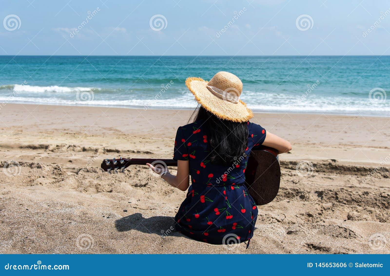 M?dchen, das Gitarre auf dem Strand spielt