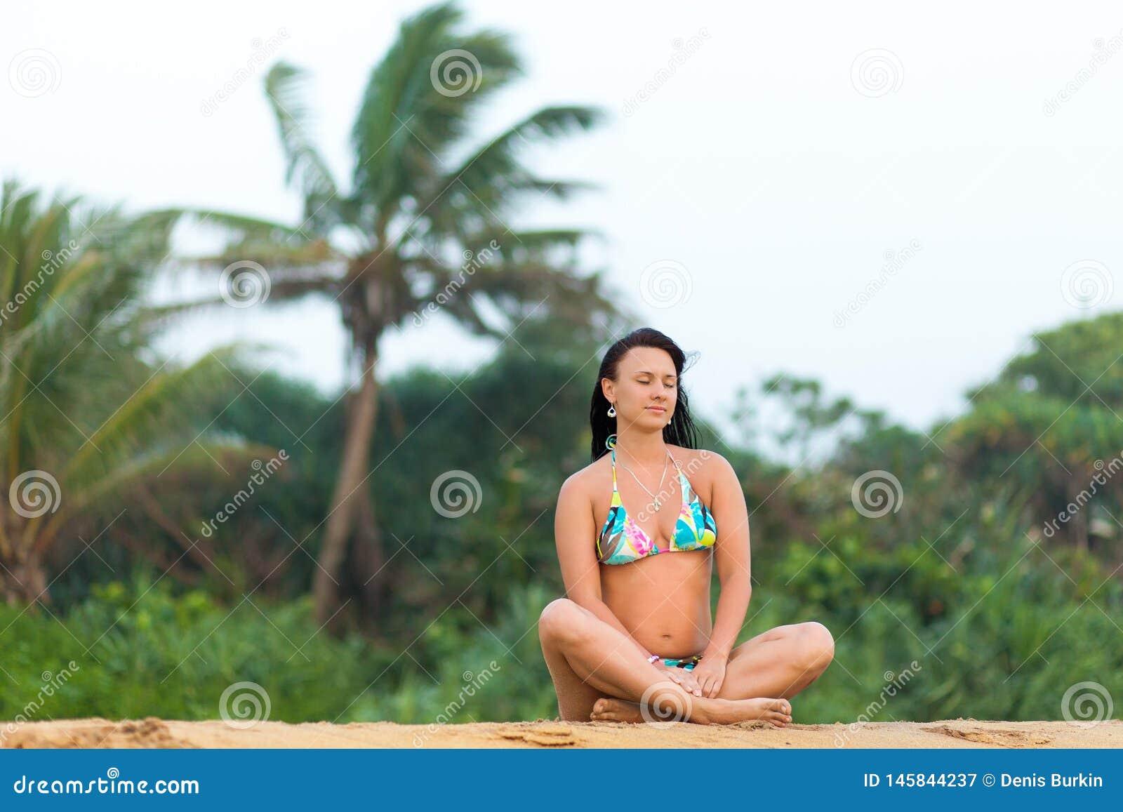 M?dchen in einem Badeanzug, der auf dem Strand Sri Lanka aufwirft ?berraschendes M?dchen in einem wei?en Badeanzug mit einer sch?