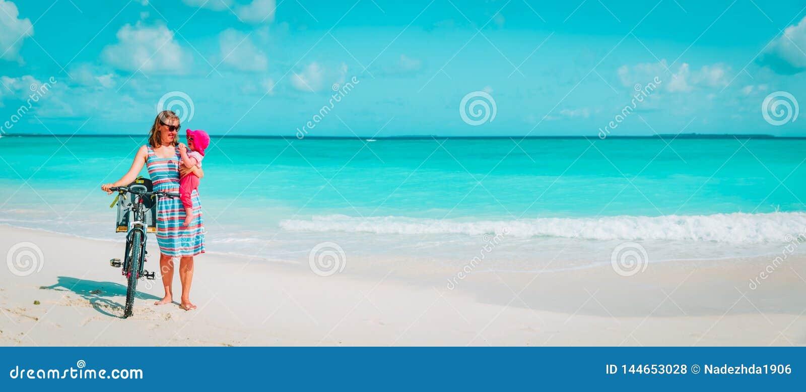 M?e feliz com a bicicleta pequena bonito do beb? na praia