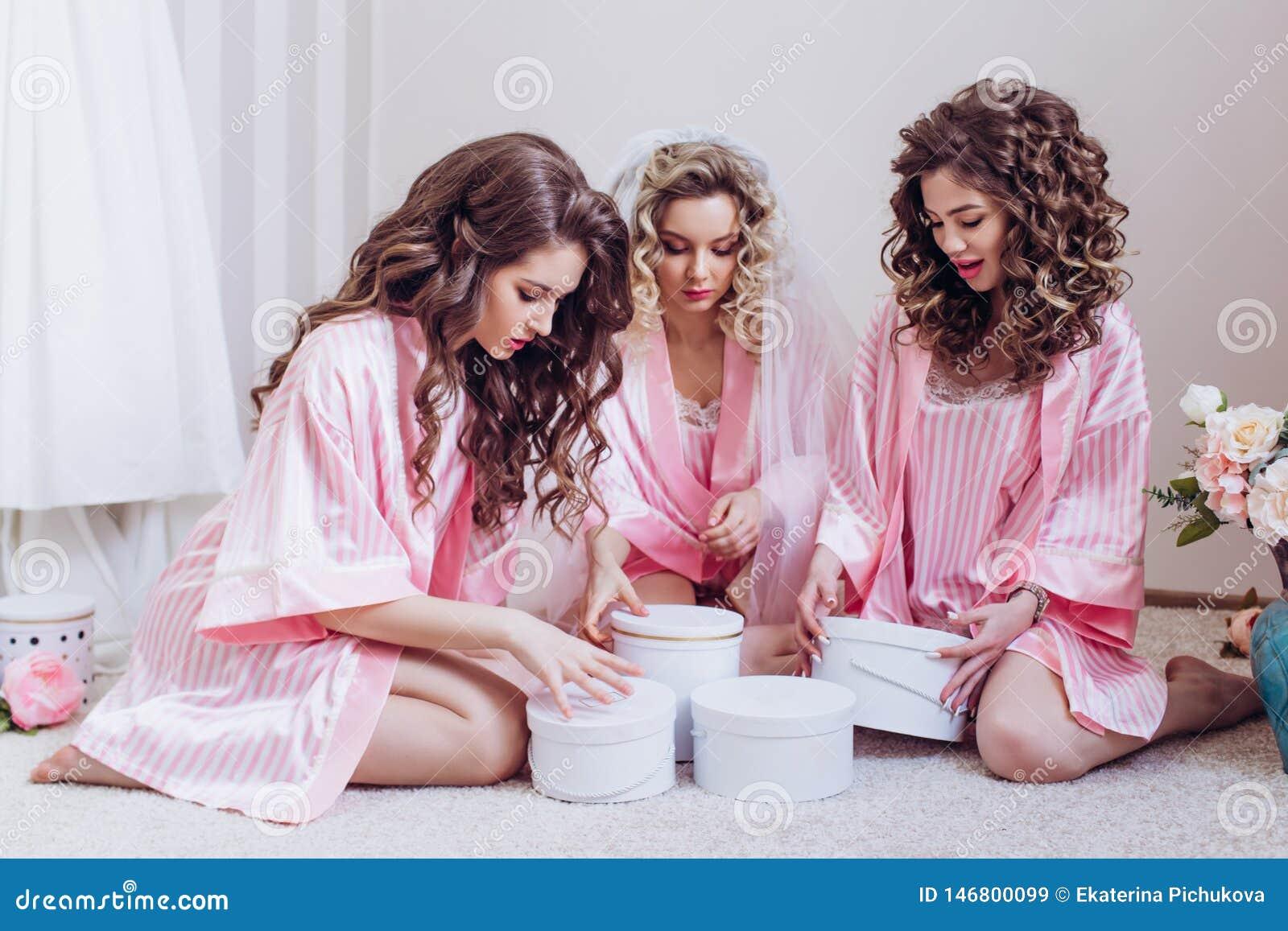 M?hippa Tre flickor firar ett ungkarlparti eller födelsedag som ger sig gåvor i rosa siden- klä kappor