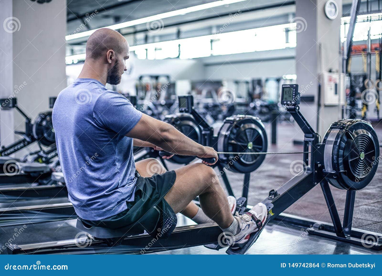 M?le utilisant la machine ? ramer au centre de fitness Jeune homme faisant des exercices sur la machine de forme physique dans le