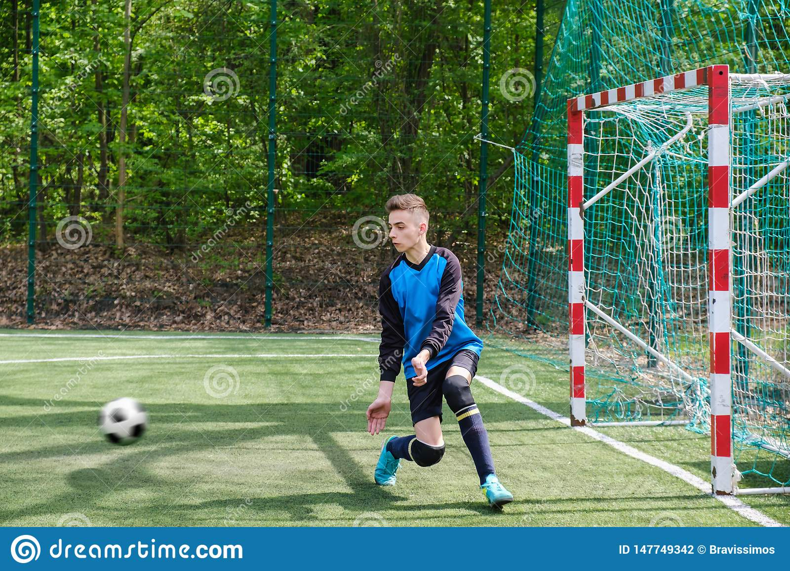 M?lvakten f?ngar bollen Stadiongoaliesportar spelar jordningsleken, mannen f?r gr?sfotbollv?rdaren, outdoorscompetition