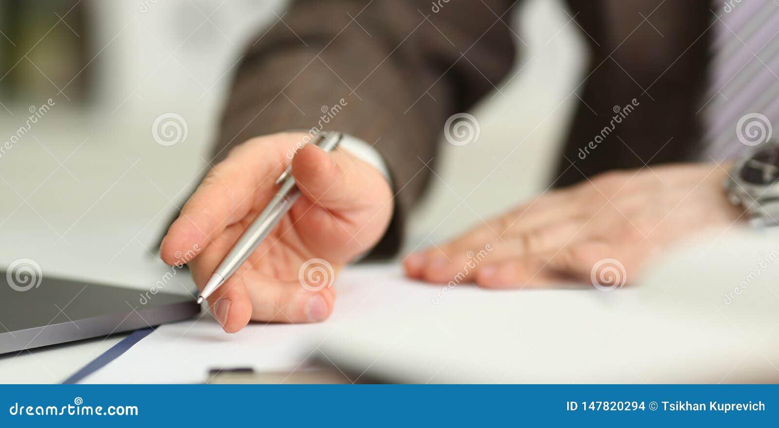 M?nnlicher Arm im Anzug und Bindung halten silbernen Stift
