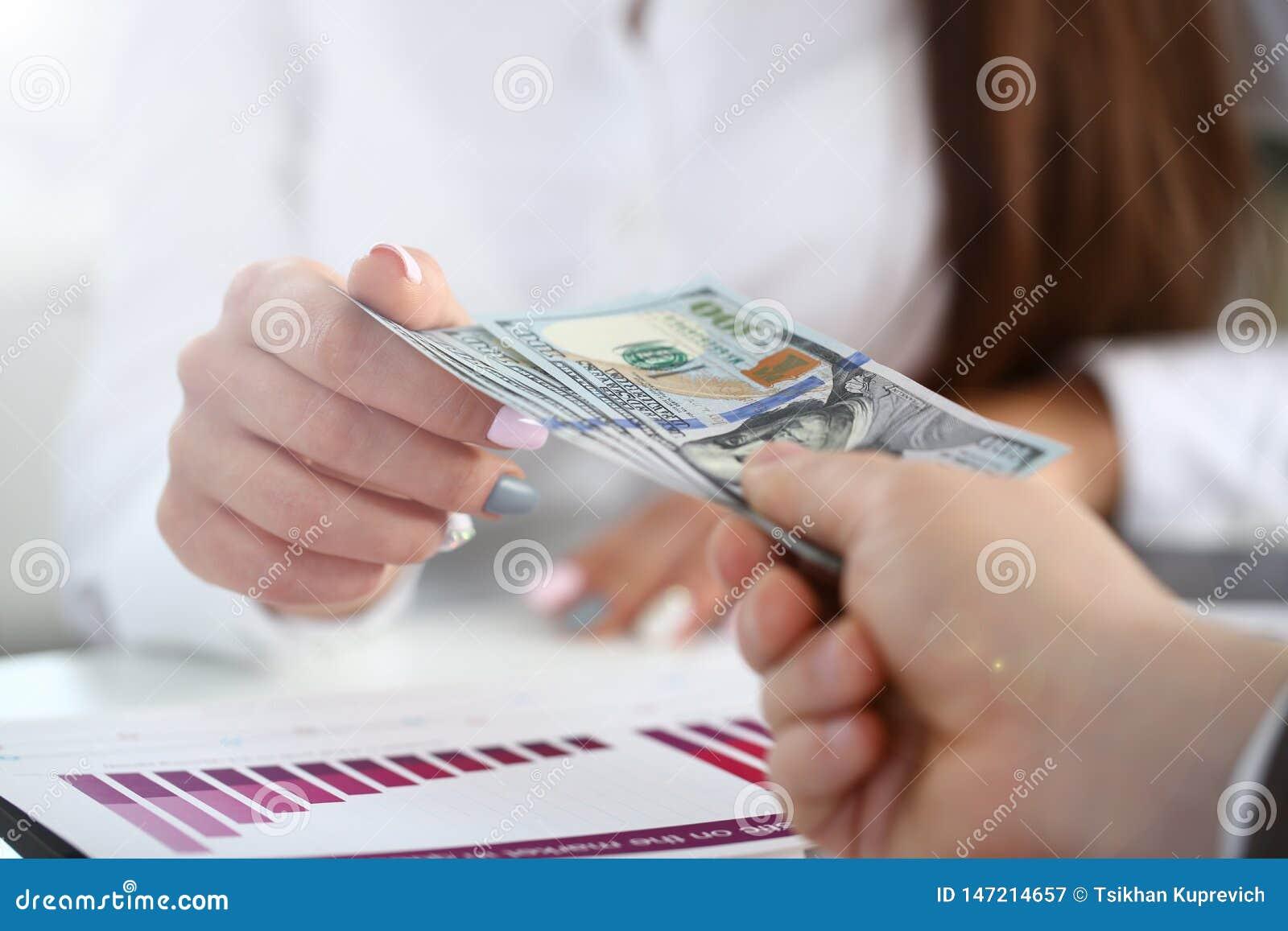 M?nnliches Armlohnb?ndel von hundert Dollarscheinen