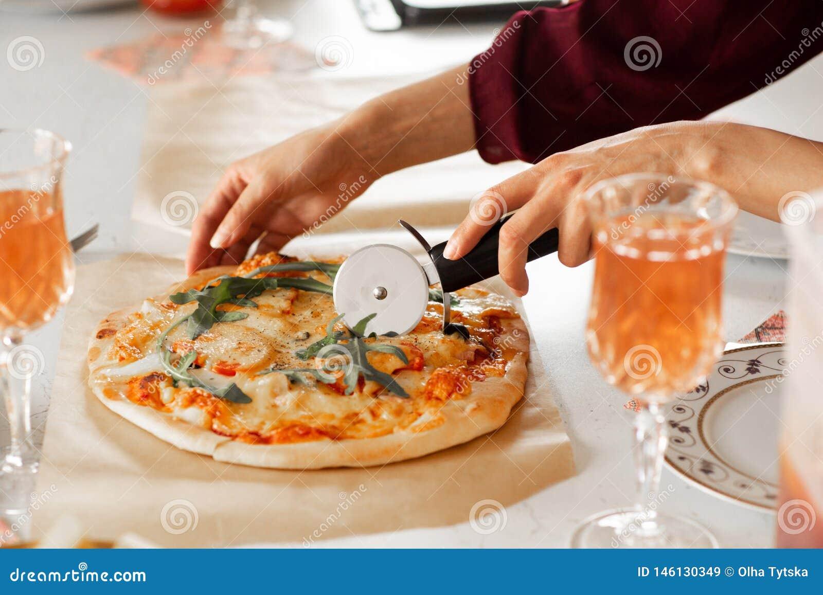 A m?o da mulher com uma faca cortou a pizza no close-up branco do fundo