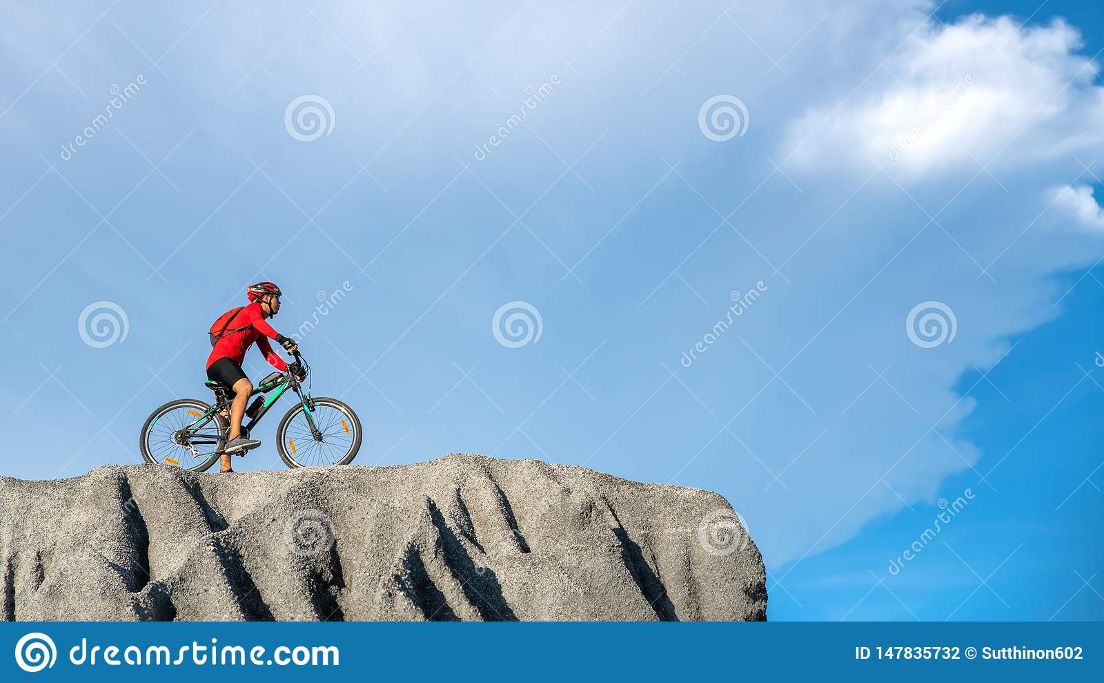 M?oda atlety pozycja na skale z bicyklem Cyklisty je?dziecki rower g?rski na skalistym ?ladzie przy zmierzchem Krańcowy roweru gó