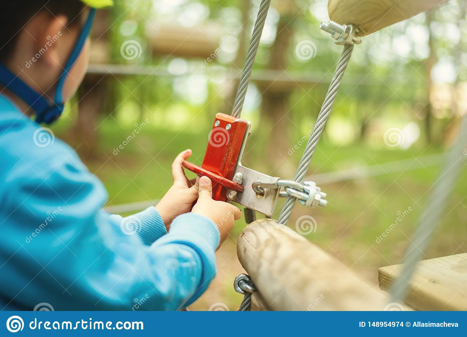 M?oda ch?opiec przechodzi kablow? tras? w?r?d drzew, kra?cowy sport w przygoda parku