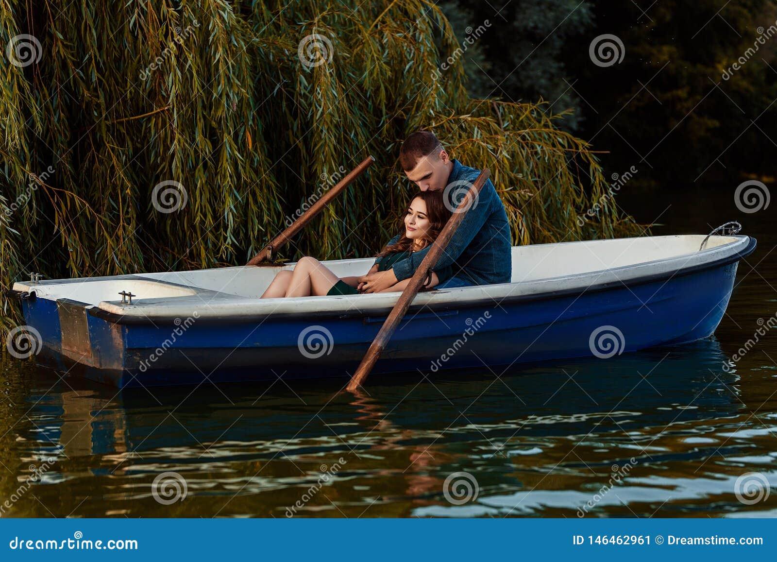 M?oda europejska para jest wodniactwo na jeziorze, m?ody cz?owiek i jego dziewczyna siedzi w ??d? przy zmierzchem, para w mi?o?ci