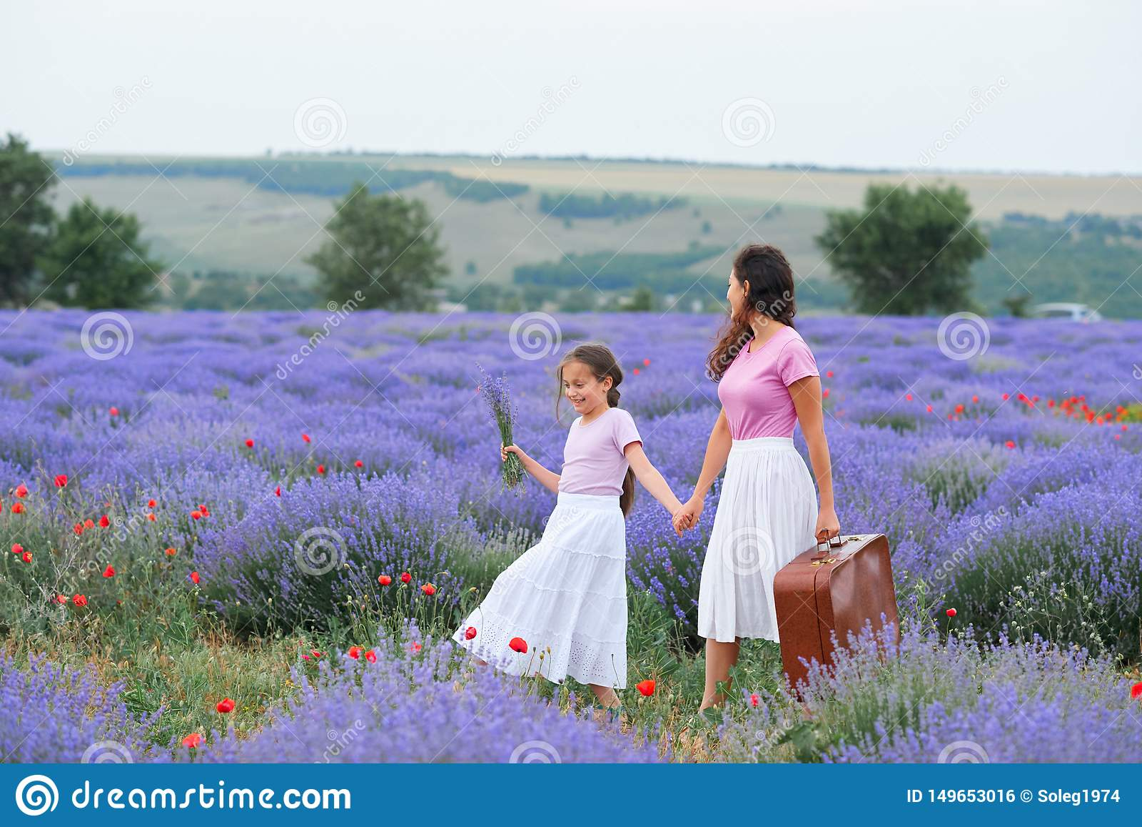 M?oda kobieta i dziewczyna chodzimy przez lawendowego kwiatu pola, pi?kny lato krajobraz