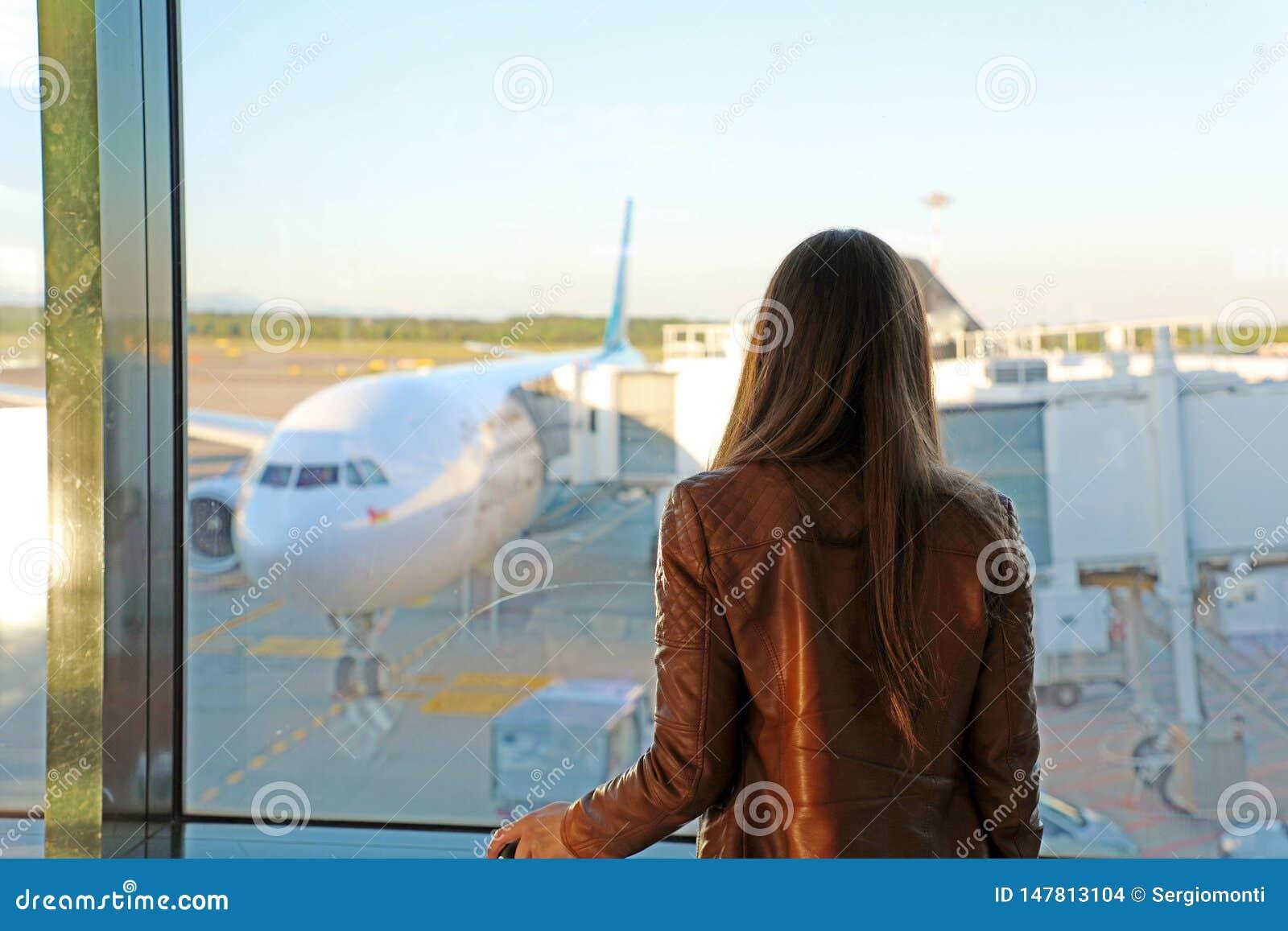 M?oda kobieta patrzeje przez okno przy samolotami w lotnisku