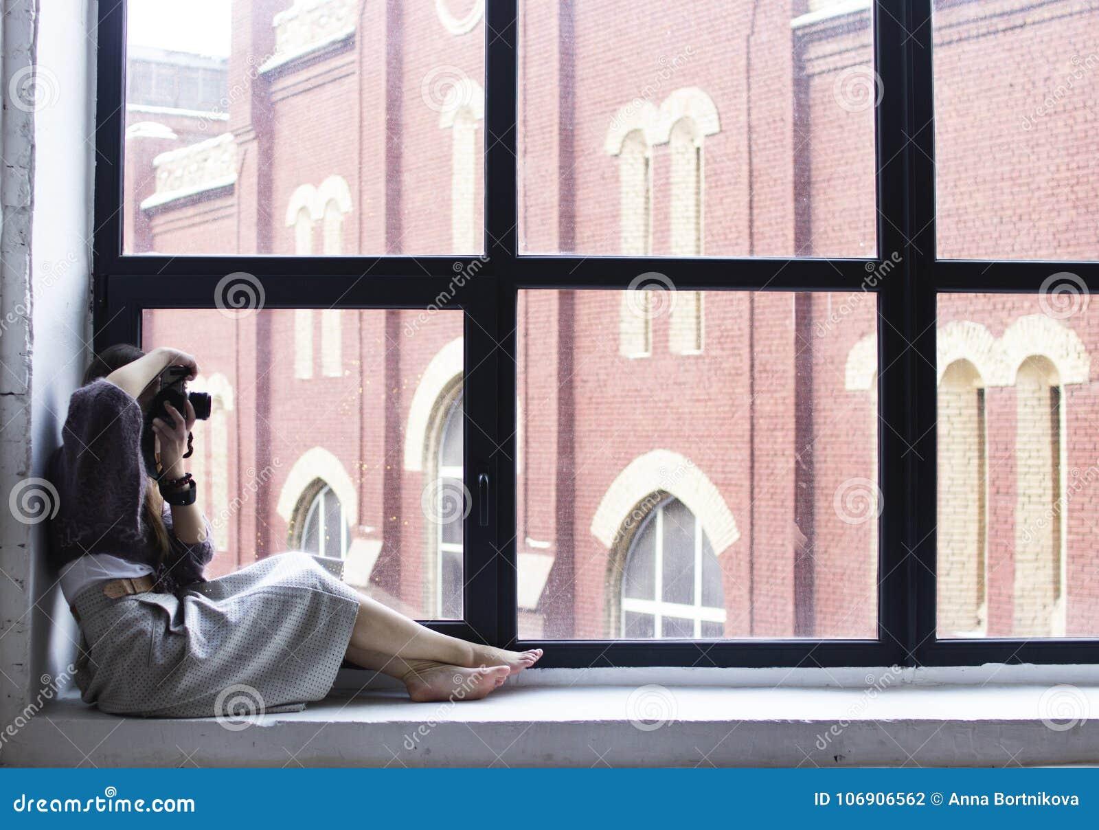 Młoda kobieta siedzi na windowsill z wielkimi okno i wp8lywy