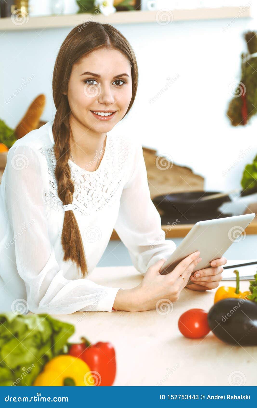 M?oda kobieta u?ywa pastylk? w kuchni podczas gdy gotuj?cy online zakupy lub robi? kamery zako?czenia twarzy dziewczyna target143