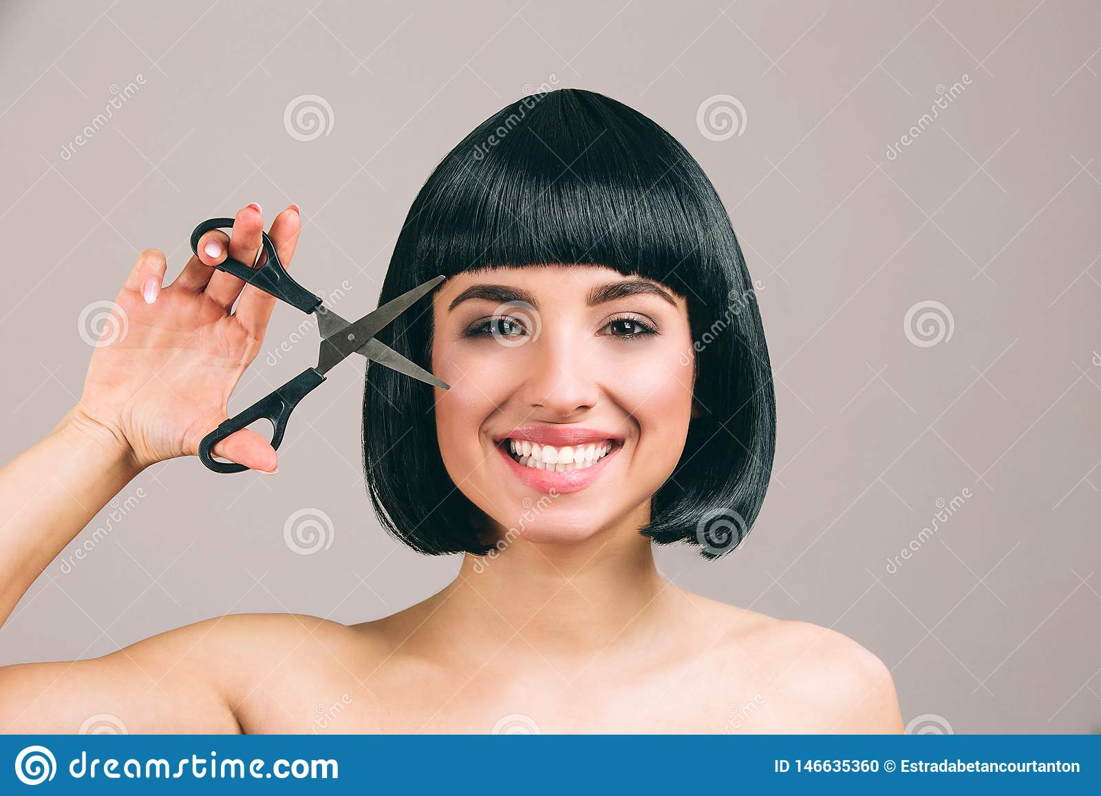 M?oda kobieta z czarni w?osy pozuje na kamerze Rozochocona ładna brunetka z koczka ostrzyżenia ono uśmiecha się Przyglądający pro