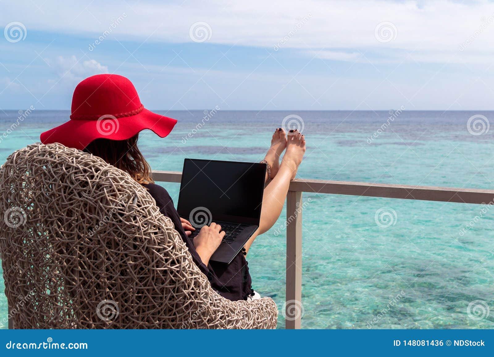 M?oda kobieta z czerwonym kapeluszowym dzia?aniem na komputerze w tropikalnym miejsce przeznaczenia