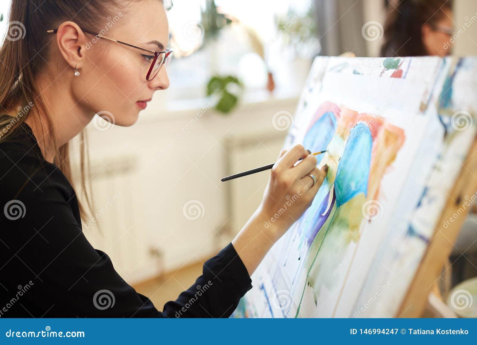 M?oda pi?kna dziewczyna w szk?ach ubieraj?cych w czarnej bluzce siedzi przy sztalug? i maluje obrazek w rysunek szkole