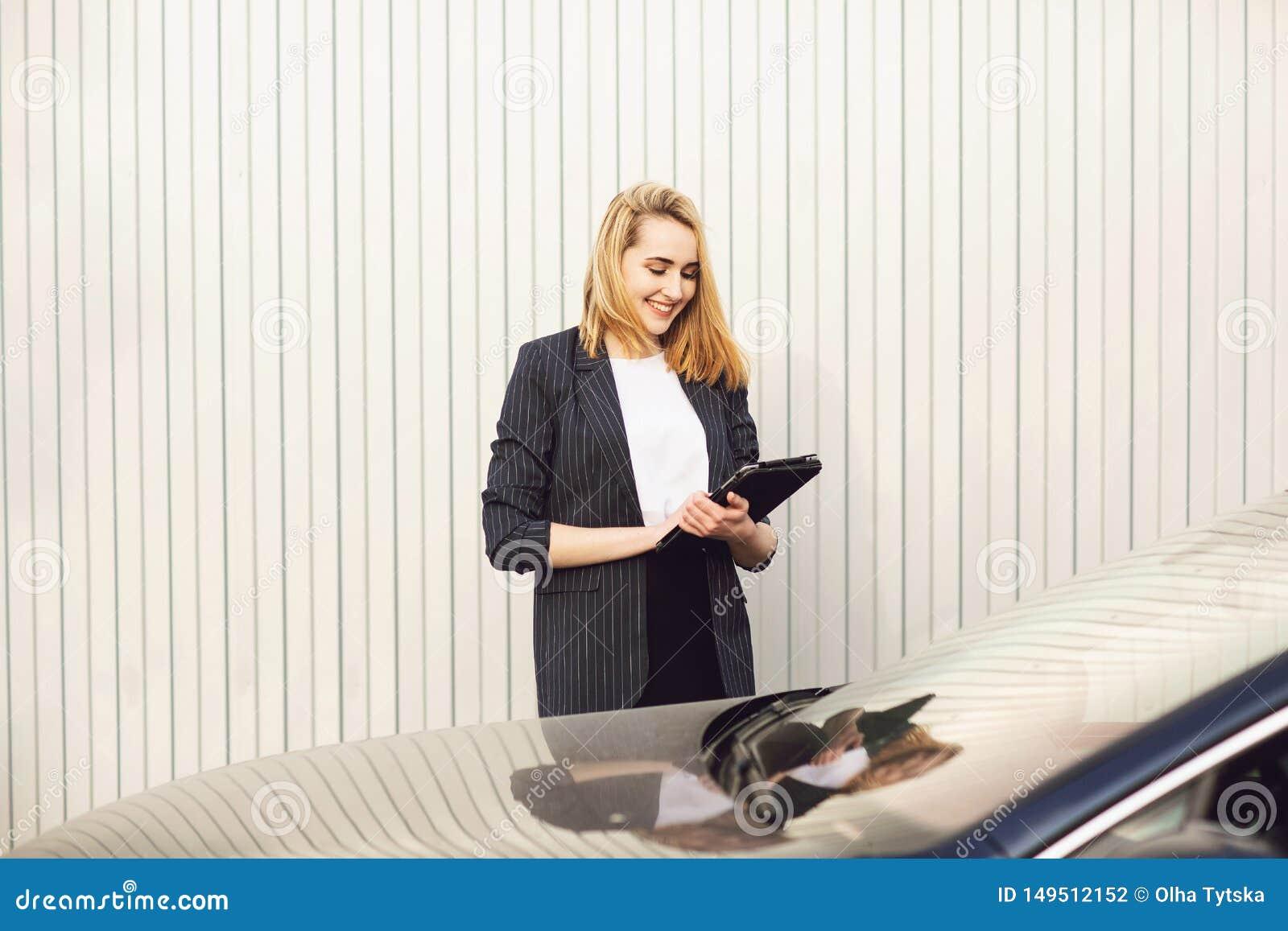 M?ody bizneswoman u?ywa pastylka komputer, podczas plenerowej kawowej przerwy, blisko budynku biurowego czarny komunikacji koncep