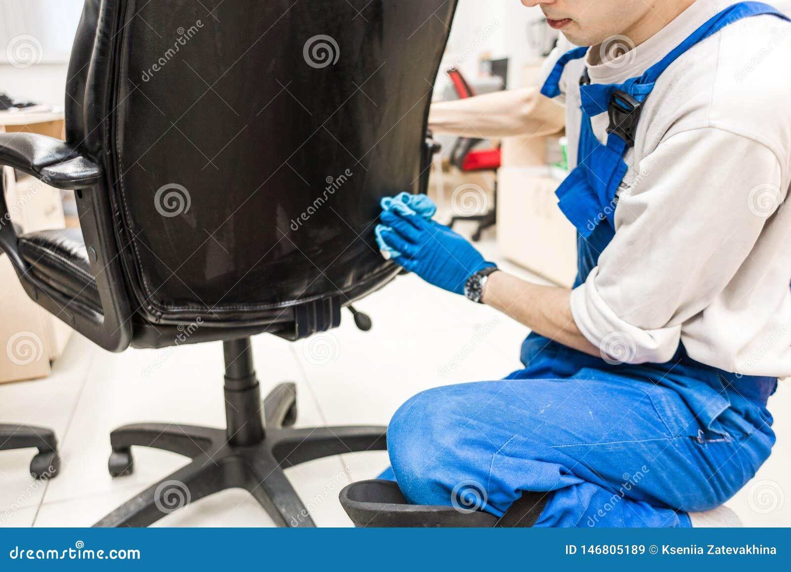 M?ody cz?owiek w workwear i gumy r?kawiczkach czy?ci biurowego krzes?a z fachowym wyposa?eniem