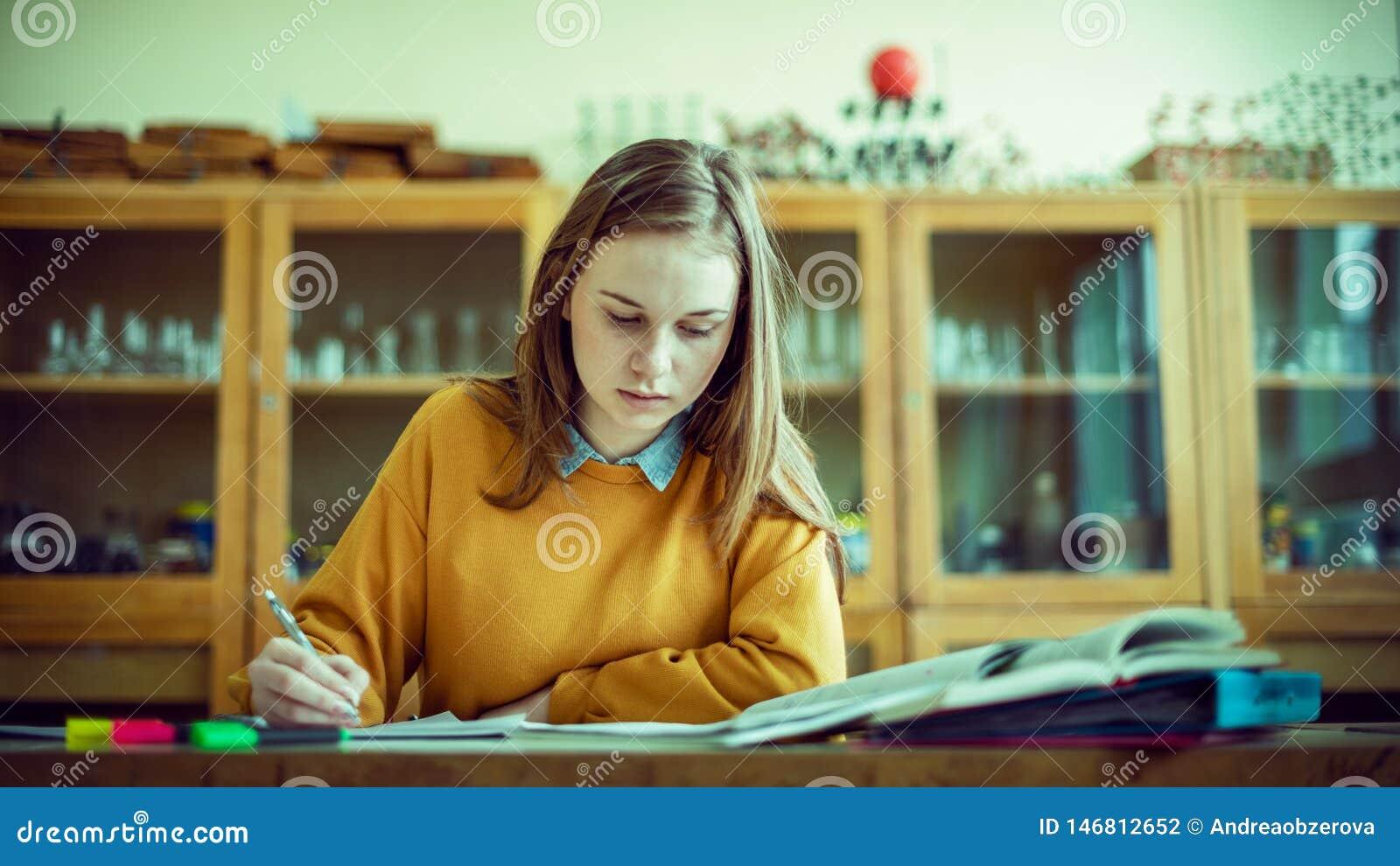 M?ody ?e?ski student collegu w chemii klasie, pisze notatkach Skupiaj?cy si? ucze? w sala lekcyjnej Autentyczny edukaci poj?cie