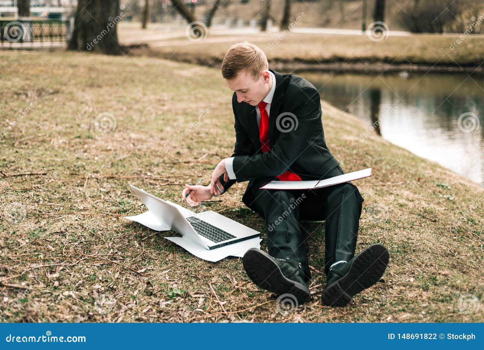 M?ody facet w czarnym kostiumu czerwonym krawacie i pisze w notatniku m??czyzna pracuje daleko w naturze w parku blisko rzeki na