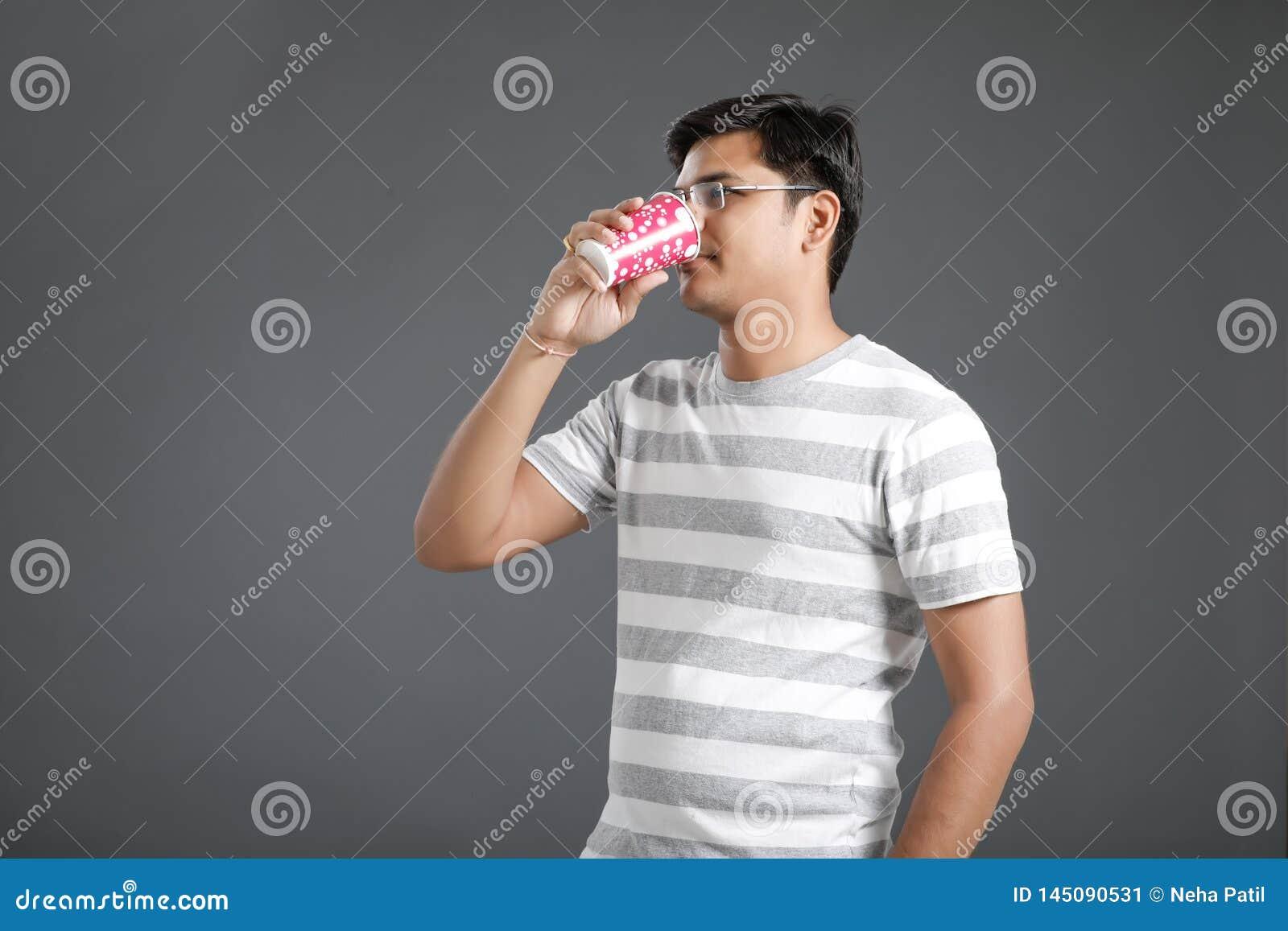 M?ody indyjski m??czyzna pije wod?