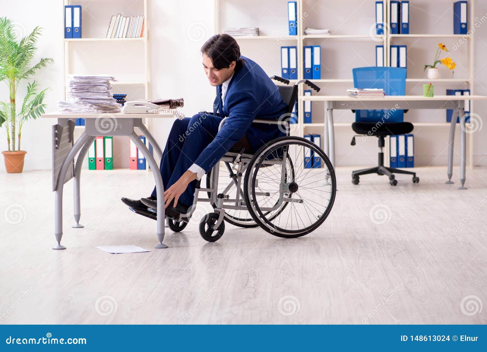 M?ody m?ski pracownik w w?zku inwalidzkim pracuje w biurze