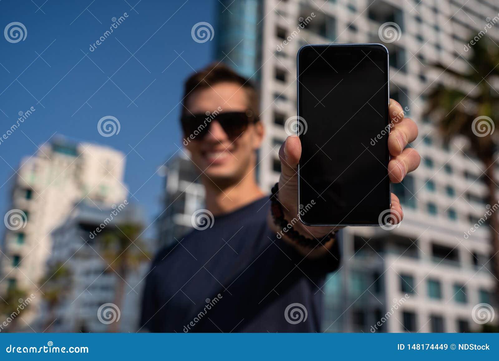 M?ody szcz??liwy m??czyzna pokazuje pionowo telefonu ekran miasta linia horyzontu jako tło