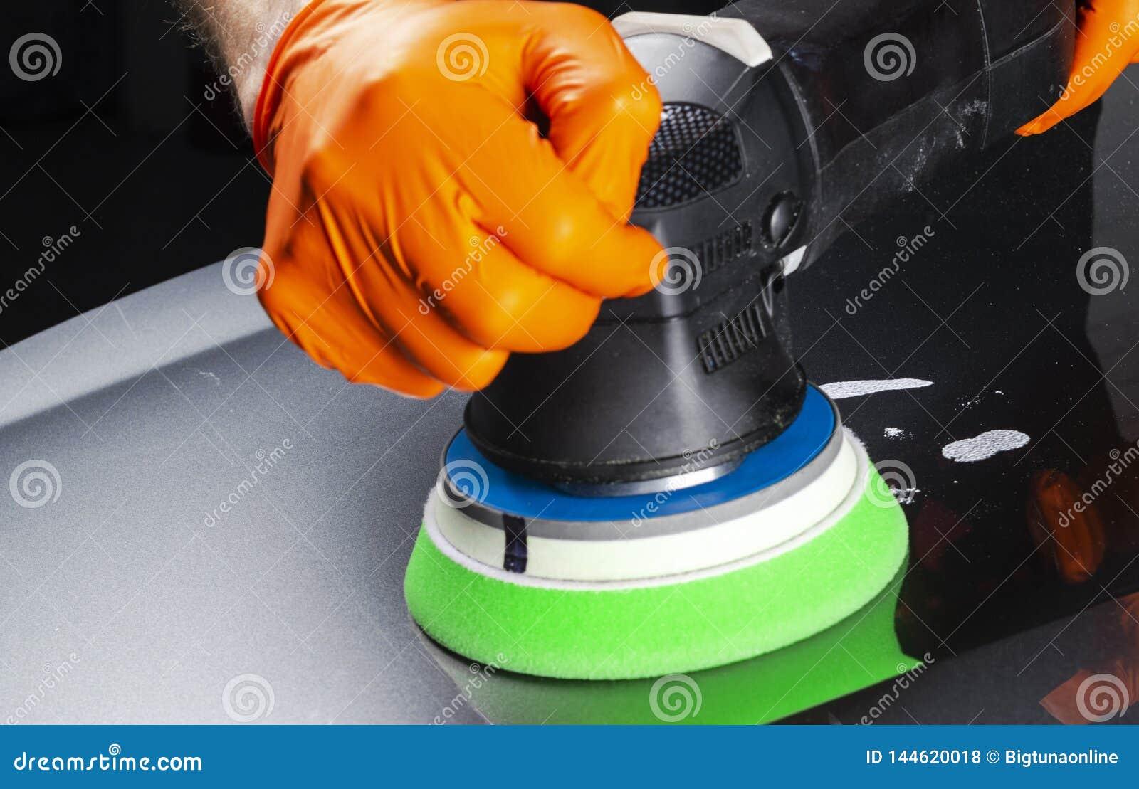 M?os polonesas do trabalhador da cera do carro que aplicam a fita protetora antes de lustrar Carro lustrando e de lustro Detalhe
