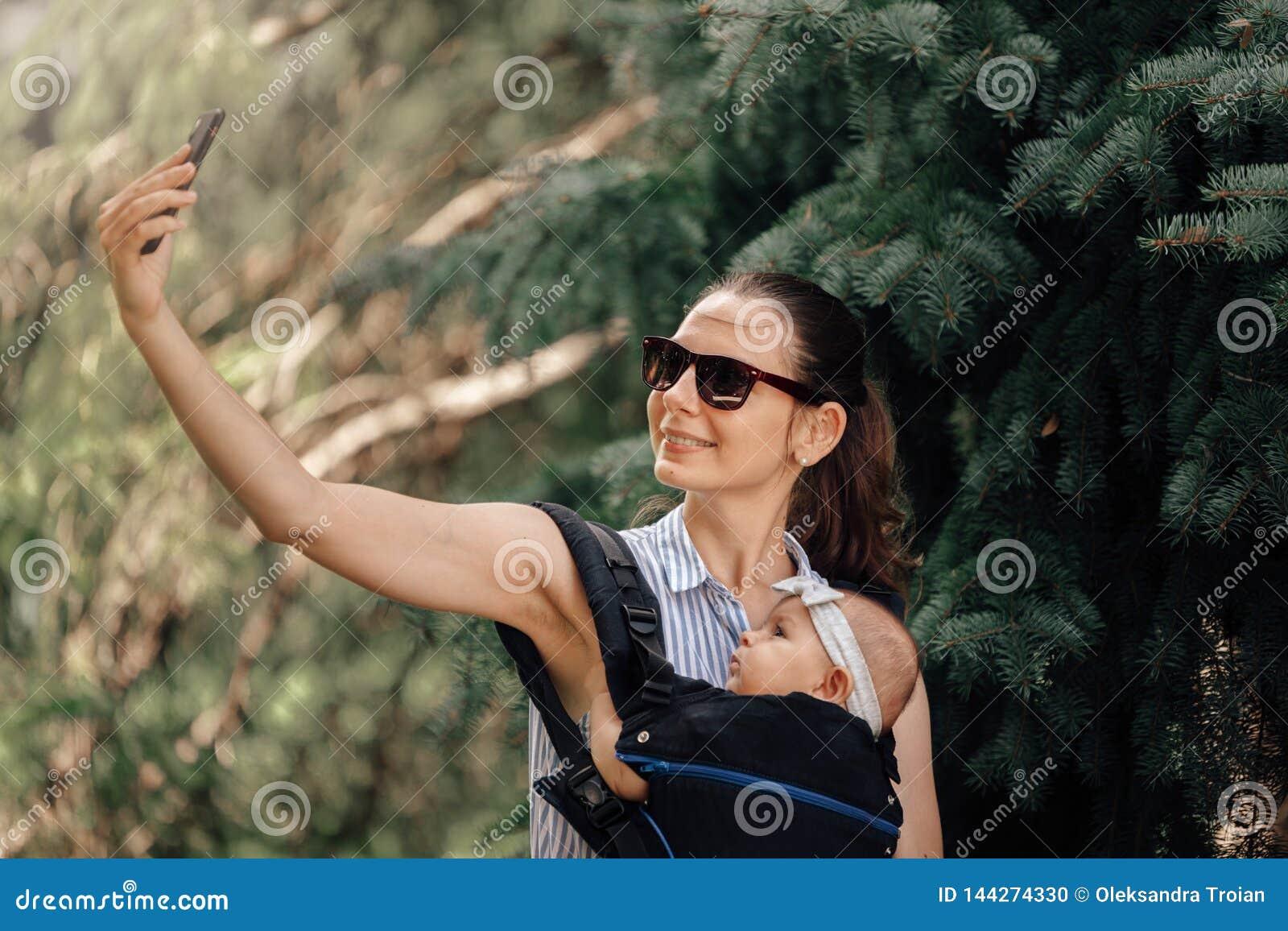 M?re avec son b?b? dans le transporteur de b?b? prenant le selfie avec le smartphone ou le blogger