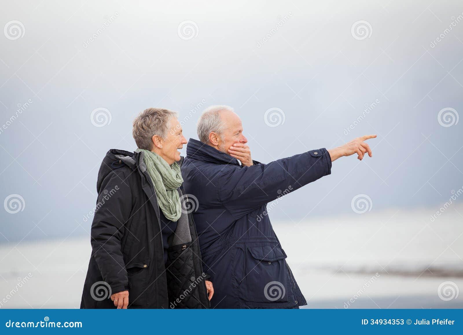 Mûrissez les couples heureux marchant sur la plage en automne